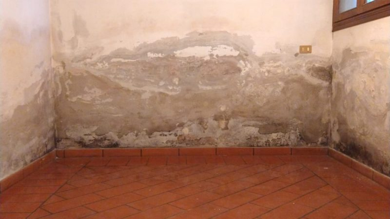 pavimento piastrelle arancioni e muro bianco scrostato